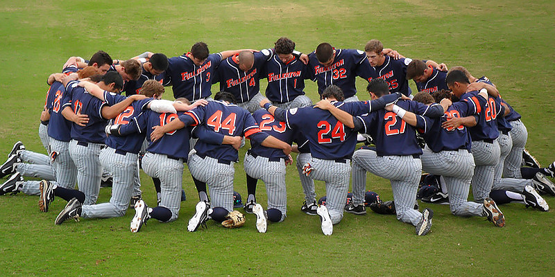 "A baseball team's group prayer, February 19, 2012. Photo by Flickr user ""arctic_whirlwind."" Available via Flickr."