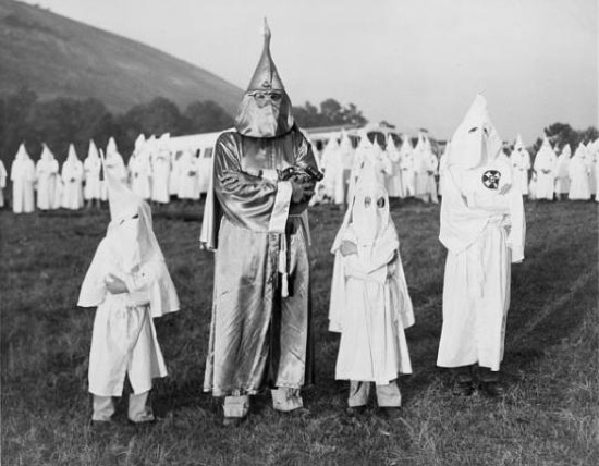 Two children wearing Ku Klux Klan robes and hoods stand on either side of Dr. Samuel Green, Ku Klux Klan Grand Dragon, at an initiation ceremony in Atlanta, Georgia. July 24, 1948. Creative Commons License by CC By 2.0