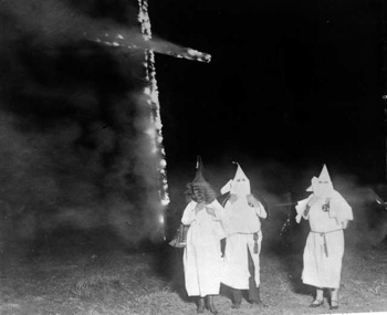 Ku Klux Klan members and a burning cross, Denver, Colorado, 1921. Creative Commons License by CC by 2.0