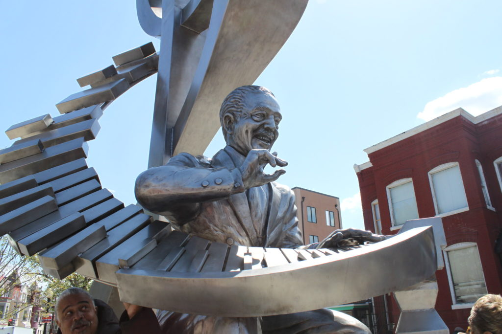 A silver statue of jazz musician Duke Ellington playing piano keys that spiral up into a treble clef