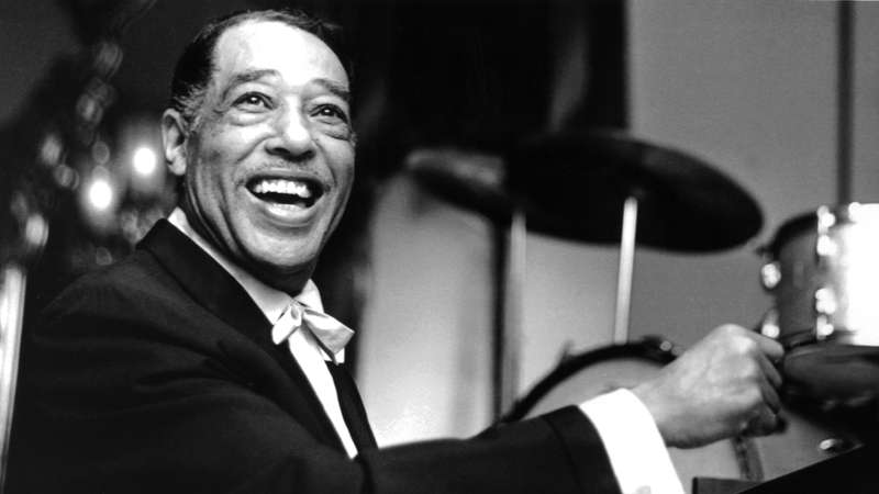 A black and white photo of jazz musician Duke Ellington smiling at the camera while sitting at a piano