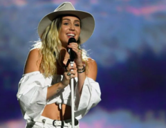Singer Miley Cyrus smiles while holding a microphone and wearing a cowboy hat